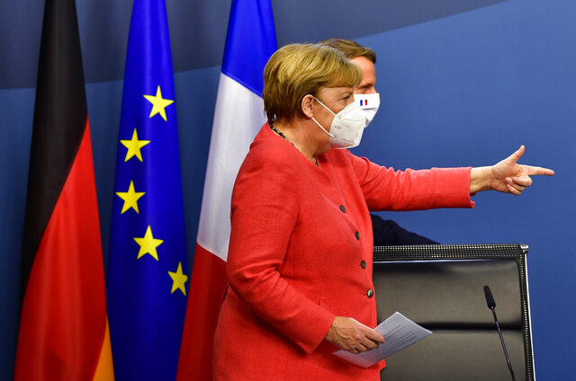 German Chancellor Angela Merkel, left, and French President Emmanuel Macron walk onto the podium prior to a media conference at the end of an EU summit in Brussels, Tuesday, July 21, 2020. Weary European Union leaders finally clinched an unprecedented budget and coronavirus recovery fund early Tuesday, finding unity after four days and as many nights of fighting and wrangling over money and power in one of their longest summits ever. (John Thys, Pool Photo via AP)