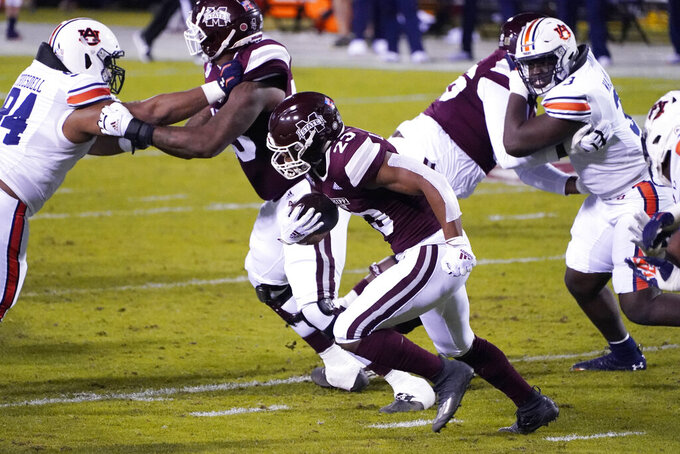 Mississippi State running back Dillon Johnson (23) runs for short yardage as Auburn defenders pursue during the first half of an NCAA college football game, Saturday, Dec. 12, 2020, in Starkville, Miss. (AP Photo/Rogelio V. Solis)