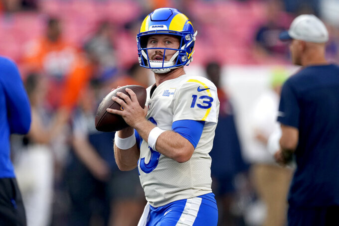 Los Angeles Rams quarterback John Wolford (13) warms up prior to an NFL preseason football game against the Denver Broncos, Saturday, Aug. 28, 2021, in Denver. (AP Photo/David Zalubowski)