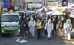 Residents spray disinfectant as a precaution against a new coronavirus at a traditional market in Suwon, South Korea, Wednesday, March 25, 2020. For most people, the new coronavirus causes only mild or moderate symptoms, such as fever and cough. For some, especially older adults and people with existing health problems, it can cause more severe illness, including pneumonia.(Kim Jong-taek/Newsis via AP)