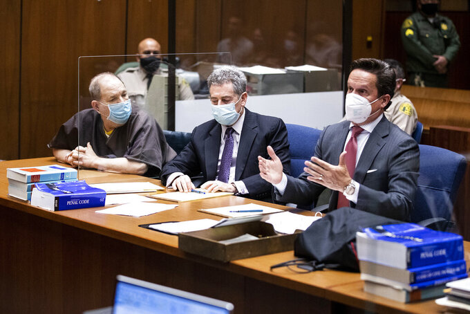 Harvey Weinstein, the 69-year-old convicted rapist and disgraced movie mogul, left, sits with his attorneys Mark Werksman, center, and attorney Alan Jackson, during a pre-trial hearing in Los Angeles, Thursday, 29 July 2021.  (Etienne Laurent/Pool Photo via AP)