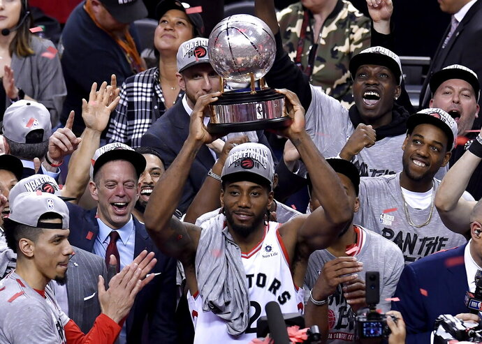 Toronto Raptors forward Kawhi Leonard (2) holds up the trophy after the team's 100-94 win over the Milwaukee Bucks in Game 6 of the NBA basketball playoffs Eastern Conference finals Saturday, May 25, 2019, in Toronto. The Raptors advanced to the NBA Finals. (Frank Gunn/The Canadian Press via AP)