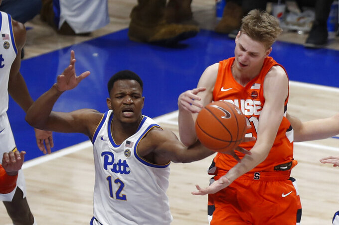 Pittsburgh's Abdoul Karim Coulibaly (12) and Syracuse's Marek Dolezaj try for a rebound during the second half of an NCAA college basketball game, Wednesday, Feb. 26, 2020, in Pittsburgh. Syracuse won 72-49.(AP Photo/Keith Srakocic)