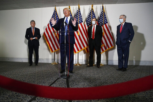 FILE - In this May 19, 2020, file photo President Donald Trump speaks with reporters after meeting with Senate Republicans at their weekly luncheon on Capitol Hill in Washington. Standing behind Trump are Sen. Roy Blunt, R-Mo., from left, Sen. John Barrasso, R-Wyo., and Senate Majority Leader Mitch McConnell of Ky. The battle for control of Congress this fall is solidifying into a race about Trump. (AP Photo/Patrick Semansky, File)