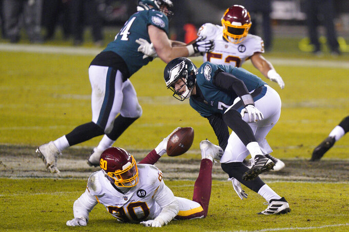 Philadelphia Eagles' Nate Sudfeld (7) and Washington Football Team's Montez Sweat (90) chase after a loose snap during the second half of an NFL football game, Sunday, Jan. 3, 2021, in Philadelphia. (AP Photo/Chris Szagola)
