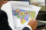 FILE - In this July 26, 2017, file photo, a lawmaker studies a district map during a joint select committee meeting on redistricting in Raleigh, N.C. Republican wins in state legislatures in 2010 put them in a commanding position to draw legislative and congressional maps the following year that essentially cemented their political power for a decade. (AP Photo/Gerry Broome, File)