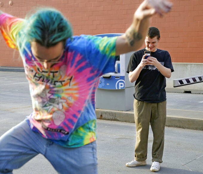 """In this Wednesday, March 10, 2021, photo Lucas Szekely, right, takes a video of Josh Sobocinski as he does skateboarding tricks in a parking lot in Greensburg, Pa. Szekely, who thought the results of November's election """"a little fishy"""" also said Democrats sending out another round of direct payments won't change that. Then added """"It's a good thing now, but you can't keep doing it forever."""" (AP Photo/Keith Srakocic)"""