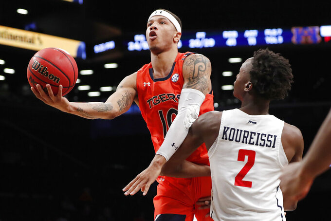Auburn guard Samir Doughty (10) goes up for a layup as he plows through the defense of Richmond forward Souleymane Koureissi (2) in the second half of an NCAA college basketball game in the Legends Classic, Tuesday, Nov. 26, 2019, in New York. Auburn defeated Richmond 79-65. (AP Photo/Kathy Willens)