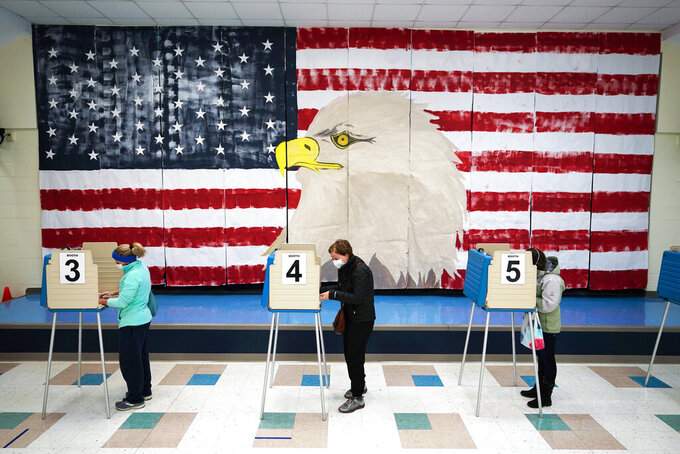 FILE - In this Nov. 3, 2020, file photo voters cast their ballots under a giant mural at Robious Elementary school on Election Day, in Midlothian, Va. As Republicans roll back access to the ballot, Democratic lawmakers have been quietly moving to expand voting rights. In Virginia, Maryland, Nevada and other states where Democrats have control, lawmakers are pushing to make it easier to cast ballots by mail, increase early voting and require greater oversight over changes to election law. (AP Photo/Steve Helber, File)