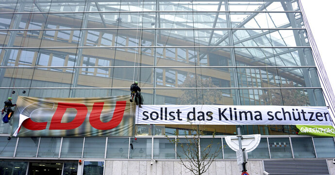 Greenpeace activists remove the 'C' of the short form 'CDU' for 'Christian Democratic Union' to create the slogan 'DU sollst das Klima schützen' ('YOU should protect the climate') during a protest at German Chancellor Angela Merkel's CDU party headquarters in Berlin, Germany, Thursday, Nov. 21, 2019. (AP Photo/Michael Sohn)