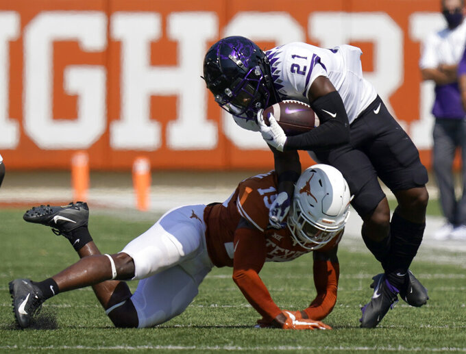 TCU running back Daimarqua Foster (21) is hit by Texas defensive back Chris Brown (15) on a run during the first half of an NCAA college football game, Saturday, Oct. 3, 2020, in Austin, Texas. (AP Photo/Eric Gay)