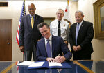 Gov. Gavin Newsom signs a measure aimed at stabilizing the state's electric utilities in the face of devastating wildfires caused by their equipment, as the bills author, Assemblyman Chris Holden, D-Pasadena, left, Thom Porter, the director for the California Department of Forestry and Fire Protection, center, and Mark Ghilarducci, the director of the California Governor's Office Emergency Services, right, look on in Sacramento, Calif., Friday, July 12, 2019. (AP Photo/Rich Pedroncelli)