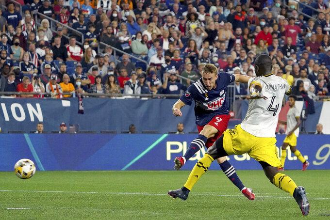 New England Revolution forward Adam Buksa (9) scores a goal ahead of Columbus Crew defender Jonathan Mensah (4) during the second half of a MLS soccer match, Saturday, Sept. 18, 2021, in Foxborough, Mass. (AP Photo/Mary Schwalm)