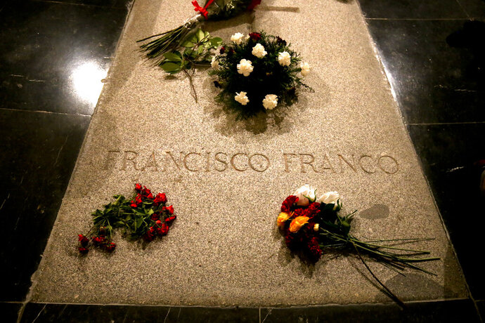 FILE - In this Friday, Aug. 24, 2018 file photo, flowers are placed on the tomb of former Spanish dictator Francisco Franco inside the basilica at the the Valley of the Fallen monument near El Escorial, outside Madrid. Spain's Socialist government has on Friday, March 15, 2019 set June 10 as the date for relocating the remains of dictator Gen. Francisco Franco from a self-aggrandizing mausoleum to a more discreet grave in a public cemetery in Madrid. (AP Photo/Andrea Comas, file)