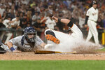 San Francisco Giants' Joe Panik, right, slides home to score as San Diego Padres catcher Austin Hedges tries to tag him during the seventh inning of a baseball game Tuesday, June 11, 2019, in San Francisco. (AP Photo/John Hefti)