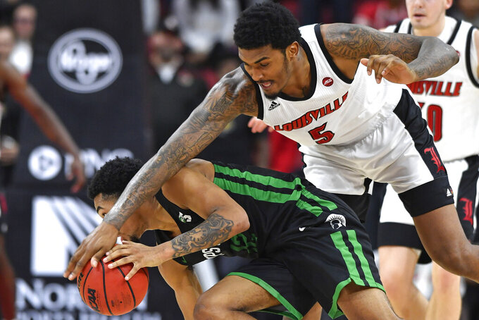 Louisville forward Malik Williams (5) attempts to knock the ball away from South Carolina Upstate guard Everette Hammond (12) during the second half of an NCAA college basketball game in Louisville, Ky., Wednesday, Nov. 20, 2019. Louisville won 76-50. (AP Photo/Timothy D. Easley)