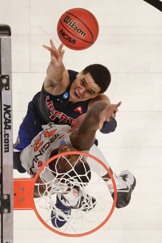 We Liberty guard Georgie Pacheco-Ortiz, top, shoots over Virginia Tech guard Ty Outlaw during the second half of a second-round game in the NCAA men's college basketball tournament Sunday, March 24, 2019, in San Jose, Calif. (AP Photo/Ben Margot)
