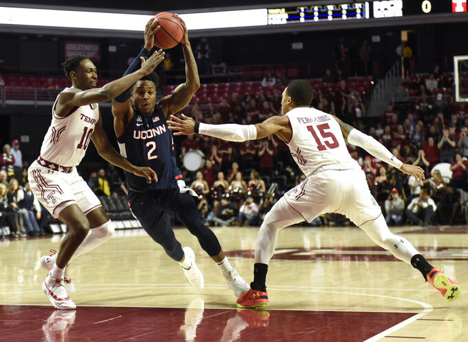 Connecticut's Tarin Smith (2) drives the ball to the basket against Temple's Shizz Alston Jr. (10) and Nate Pierre-Louis (15) during the first half of an NCAA college basketball game, Wednesday, Feb. 6, 2019, in Philadelphia. (AP Photo/Michael Perez)