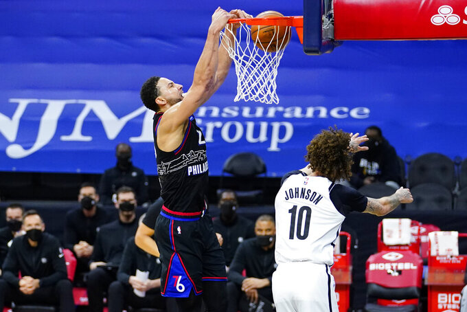 Philadelphia 76ers' Ben Simmons, left, dunks the ball against Brooklyn Nets' Iman Shumpert during the second half of an NBA basketball game, Saturday, Feb. 6, 2021, in Philadelphia. (AP Photo/Matt Slocum)