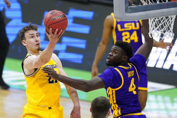 Michigan guard Franz Wagner, left, drives to the basket over LSU forward Darius Days (4) during the first half of a second-round game in the NCAA men's college basketball tournament at Lucas Oil Stadium Monday, March 22, 2021, in Indianapolis. (AP Photo/Darron Cummings)