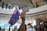 """FILE - In this Friday, May 29, 2020 file photo, protesters hold a British National (Overseas) passport and Hong Kong colonial flag in a shopping mall during a protest against China's national security legislation for the city, in Hong Kong. Only five years ago, former British Prime Minister David Cameron was celebrating a """"golden era"""" in U.K.-China relations, bonding with President Xi Jinping over a pint of beer at the pub and signing off trade deals worth billions. Those friendly scenes now seem like a distant memory, with hostile rhetoric ratcheting up this week over Beijing's new national security law on Hong Kong. China has threatened """"consequences"""" after Britain offered refuge to millions in the former colony. (AP Photo/Kin Cheung, file)"""