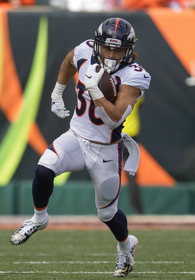 FILE - In this Dec. 2, 2018, file photo, Denver Broncos running back Phillip Lindsay (30) runs with the ball during the first half of the NFL football game against the Cincinnati Bengals, in Cincinnati. He didn't get invited to the NFL combine and wasn't selected in the NFL draft. Then, an injury threatened to keep Phillip Lindsay from the spoils of his sensational season, the Pro Bowl. Although he won't be playing, the Denver Broncos rookie running back is attending the league's annual all-star game as a social media correspondent for the league. (AP Photo/Bryan Woolston, File)