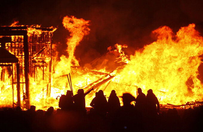 """FILE - In this Sept. 3, 2016, file photo, attendees are silhouetted as the structure of the """"Man"""" burns during Burning Man at the Black Rock Desert of Gerlach, Nev., north of Reno. Burning Man organizers announced Tuesday, April 27, 2021, they are canceling this summer's annual counter-culture festival in the Nevada desert for the second year in a row due to the COVID-19 pandemic. (Chase Stevens/Las Vegas Review-Journal via AP, File)"""