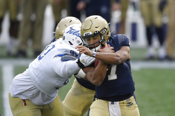 Navy quarterback Xavier Arline (7) is pressured by Tulsa defensive lineman Jaxon Player (90) during the first half of an NCAA college football game, Saturday, Dec. 5, 2020, in Annapolis, Md. (AP Photo/Nick Wass)