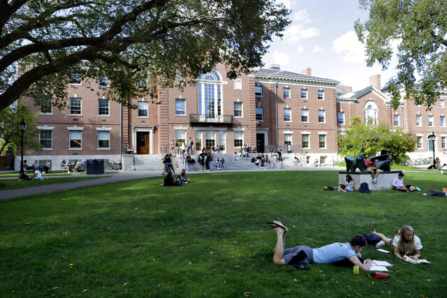 FILE - In this Sept. 25, 2019, file photo, people rest on grass while reading at Brown University in Providence, R.I. Brown is rebutting what the Ivy League school calls