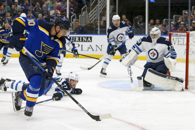 Winnipeg Jets goaltender Connor Hellebuyck (37) protects the goal while teammate Nikolaj Ehlers (27), of Denmark, reaches out for St. Louis Blues' Brayden Schenn (10) during the second period of an NHL hockey game Thursday Feb. 6, 2020, in St. Louis. (AP Photo/Scott Kane)