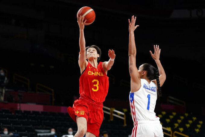 China's Liwei Yang (3) drives on Puerto Rico's Tayra Melendez (1) during a women's basketball preliminary round game at the 2020 Summer Olympics in Saitama, Japan, Tuesday, July 27, 2021. (AP Photo/Charlie Neibergall)