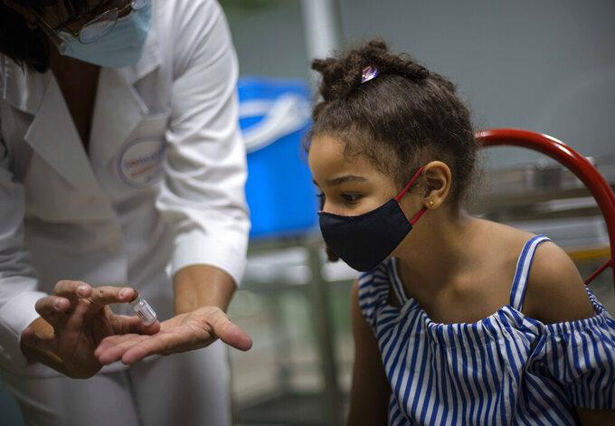 A nurse shows a vial of the Cuban made Soberana-02 vaccine for COVID-19 before giving a girl a dose of it in Havana, Cuba, Tuesday, Aug. 24, 2021. (AP Photo/Ramon Espinosa)
