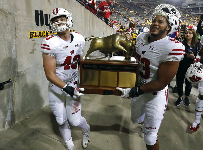 FILE - In this Sept. 22, 2018 file photo Wisconsin linebackers Ryan Connelly, left, and T.J. Edwards, carry the Heartland Trophy off the field after the team's win over Iowa in an NCAA college football game in Iowa City. Edwards and Connelly will look to steady the banged-up Wisconsin defense against Rutgers on Saturday, Nov. 3, 2018. The Badgers will be without another key player against the Scarlet Knights with Olive Sagapolu out with a right arm injury. Edwards and Connelly have been playmaking rocks in the lineup. The defense will be facing a Rutgers team that is last out of the 129 major college football schools in scoring at 15.1 points per game. (AP Photo/Matthew Putney)