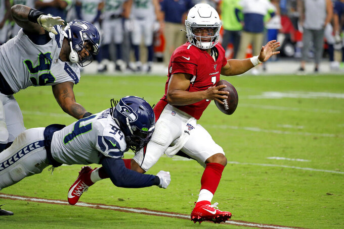 Arizona Cardinals quarterback Kyler Murray (1) is tackled by Seattle Seahawks defensive end Ezekiel Ansah (94) as defensive tackle Quinton Jefferson (99) pursues during the second half of an NFL football game, Sunday, Sept. 29, 2019, in Glendale, Ariz. (AP Photo/Ross D. Franklin)