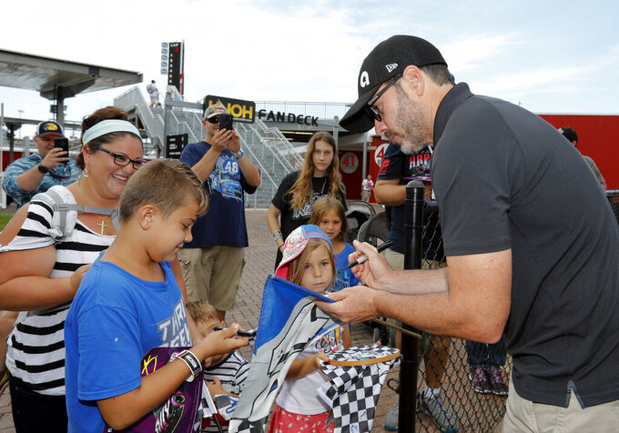 Jimmie Johnson, right, gives autographs to fans after a NASCAR auto race news conference at Daytona International Speedway, Friday, July 5, 2019, in Daytona Beach, Fla. (AP Photo/Terry Renna)