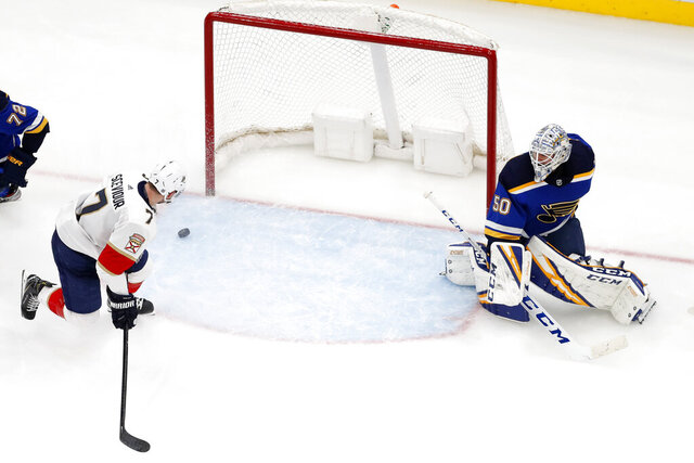Florida Panthers' Colton Sceviour, left, watches a puck slide past St. Louis Blues goaltender Jordan Binnington during the second period of an NHL hockey game Monday, March 9, 2020, in St. Louis. (AP Photo/Jeff Roberson)