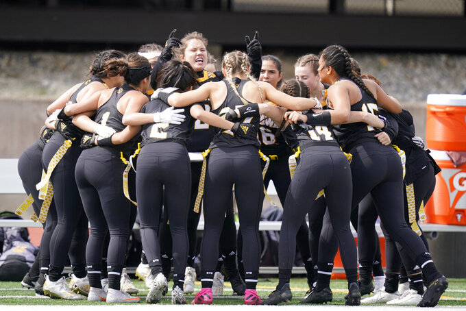 Ottawa University women's flag football team cheers before an NAIA flag football game against Midland University in Ottawa, Kan., Friday, March 26, 2021. The National Association of Intercollegiate Athletics introduced women's flag football as an emerging sport this spring. (AP Photo/Orlin Wagner)