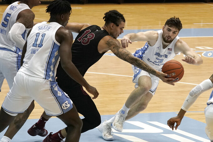 North Carolina guard Andrew Platek (3) and North Carolina Central forward Justin Whatley (13) chase the ball during the second half of an NCAA college basketball game in Chapel Hill, N.C., Saturday, Dec. 12, 2020. (AP Photo/Gerry Broome)