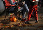 In this Saturday, Oct. 26, 2019 photo a carved Halloween pumpkin is placed next to a bench at The Halloween Pumpkin Fest in Bucharest, Romania. (AP Photo/Vadim Ghirda)