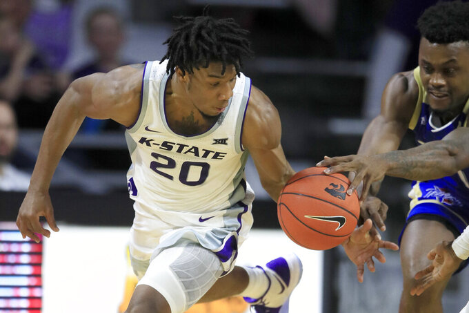 Kansas State forward Xavier Sneed (20) takes the ball from Tulsa forward Martins Igbanu, right, during the second half of an NCAA college basketball game in Manhattan, Kan., Sunday, Dec. 29, 2019. (AP Photo/Orlin Wagner)