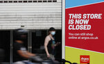 A woman looks at her phone as she walks past a closed branch of Argos in Kensington, London, Wednesday, Aug. 12, 2020. The British economy is on course to record the deepest coronavirus-related slump among the world's seven leading industrial economies after official figures showed it shrinking by a 20.4% in the second quarter of 2020 alone said The Office for National Statistics. (AP Photo/Alastair Grant)