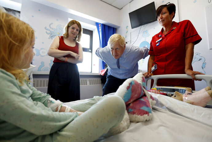 Britain's Prime Minister Boris Johnson talks to hospital patient Scarlett Gibbons, 5, during a visit to the Royal Cornwall Hospital in Truro, south-west England, Monday Aug. 19, 2019.   Johnson is under increasing pressure Monday to recall Parliament after leaked government documents warned of widespread problems if the U.K. leaves the European Union without a Brexit withdrawal agreement. (Peter Nicholls/Pool via AP)