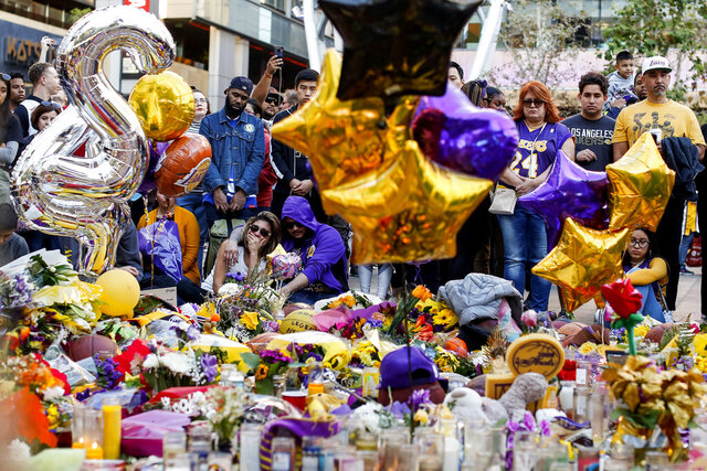 Fans pay respect at a memorial for Kobe Bryant near Staples Center Tuesday, Jan. 28, 2020, in Los Angeles. Bryant, the 18-time NBA All-Star who won five championships and became one of the greatest basketball players of his generation during a 20-year career with the Los Angeles Lakers, died in a helicopter crash Sunday. (AP Photo/Ringo H.W. Chiu)