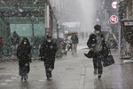 Pedestrians wearing face masks to help protect against the spread of the coronavirus move through the falling snow in Seoul, South Korea, Thursday, Jan. 28, 2021. (AP Photo/Ahn Young-joon)