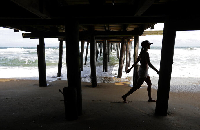A lady walks under a pier while the surf rises Wednesday, Sept. 12, 2018, in Kill Devil Hills, N.C., as Hurricane Florence approaches the east coast. (AP Photo/Gerry Broome)