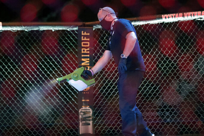 A worker sprays sanitizer in the octagon between bouts during a UFC 249 mixed martial arts competition, Saturday, May 9, 2020, in Jacksonville, Fla. (AP Photo/John Raoux)