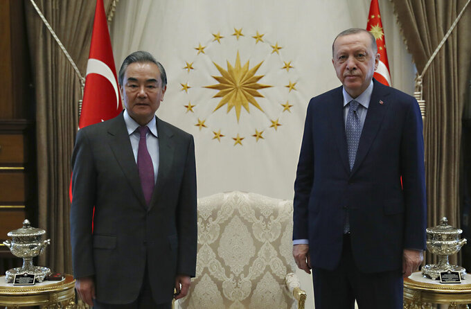 Turkey's President Recep Tayyip Erdogan, right, and Chinese Foreign Minister Wang Yi pose for photos before a meeting, in Ankara, Turkey, Thursday, March 25, 2021. Hundreds of Uyghurs staged protests in Ankara and Istanbul on Thursday, denouncing Wang Yi's visit to Turkey and demanding that the Turkish government take a stronger stance against human rights abuses in China's far-western Xinjiang region. (Turkish Presidency via AP, Pool)