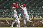Cincinnati Reds' Mike Moustakas, right, celebrates with Jesse Winker after hitting three-run home run against the Chicago Cubs during the first inning of a baseball game Wednesday, Sept. 9, 2020, in Chicago. (AP Photo/Kamil Krzaczynski)