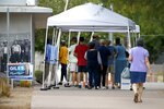 Voters line up at the Tempe Public Library to cast ballots in the primary election Tuesday, Aug. 4, 2020, in Tempe, Ariz. (AP Photo/Ross D. Franklin)