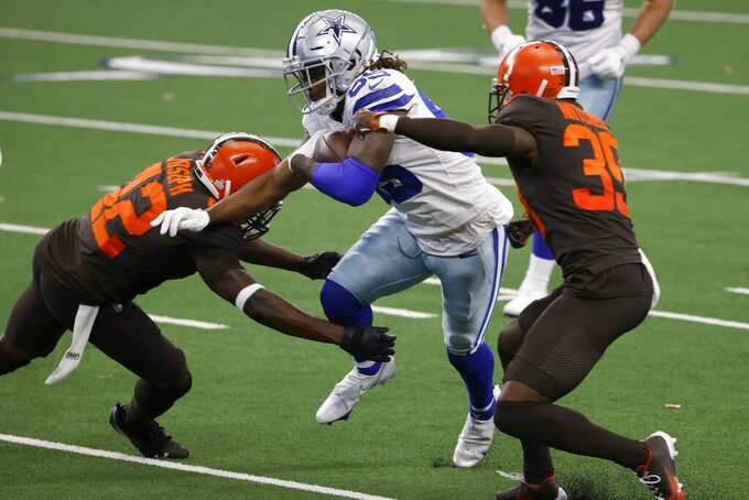 Cleveland Browns' Karl Joseph (42) and Terrance Mitchell (39) attempt to make the stop as Dallas Cowboys wide receiver Noah Brown (85) gains yardage after making a catch in the second half of an NFL football game in Arlington, Texas, Sunday, Oct. 4, 2020. (AP Photo/Ron Jenkins)